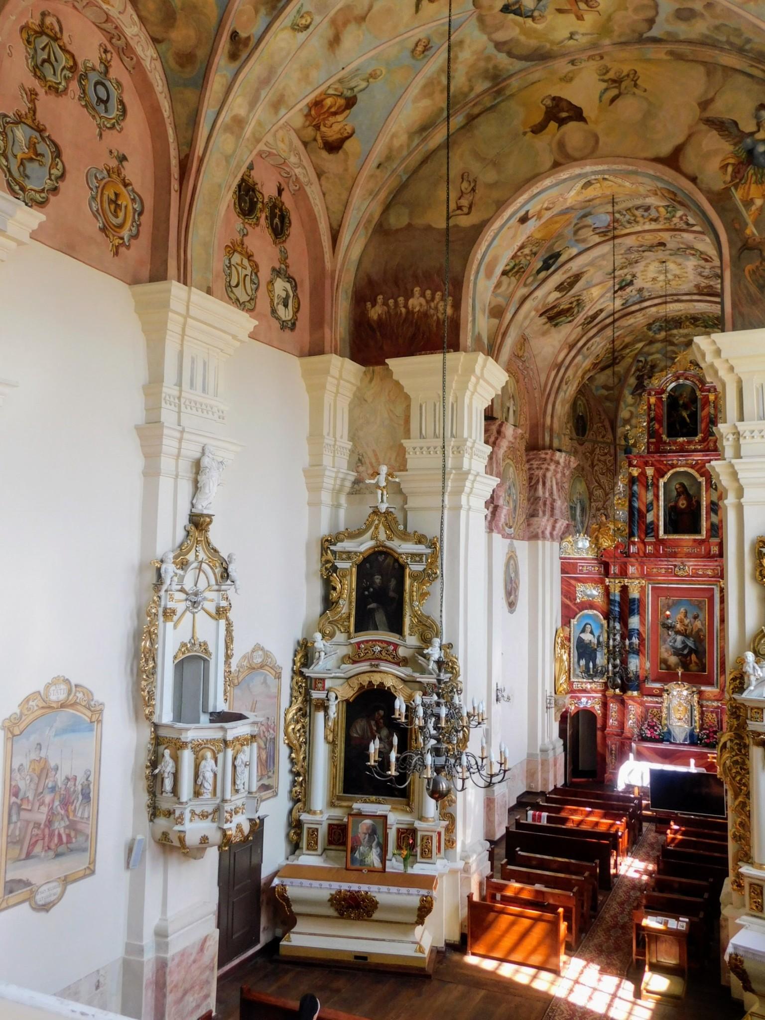 widok nawy z odrestaurowanymi freskami i stacjami drogi krzyżowej